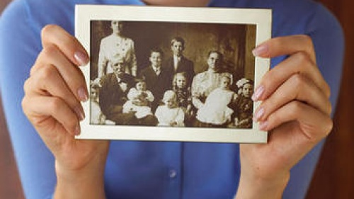A woman holding an old family photo.