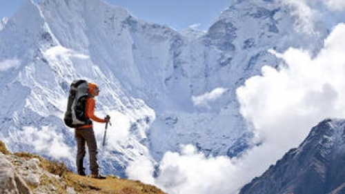 A hiker on top of a mountain pass.