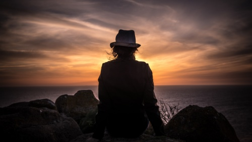 A person sitting on a rock looking over water - orange sunset.