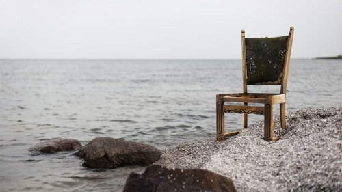 A chair sitting by a lake.