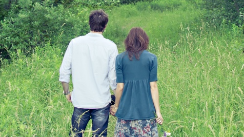 A young married couple holding hands standing in a grass field.