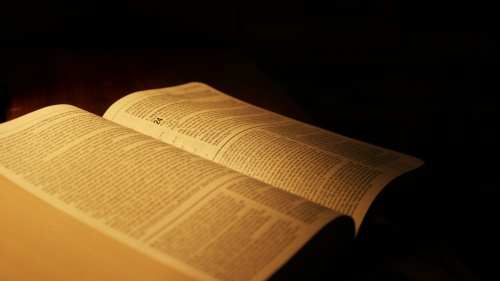 An open Bible in a dark room.