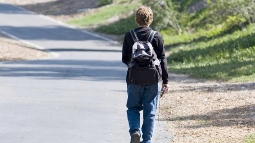 A young boy walking away wearing a backpack.