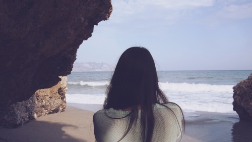 Woman looks at the ocean.
