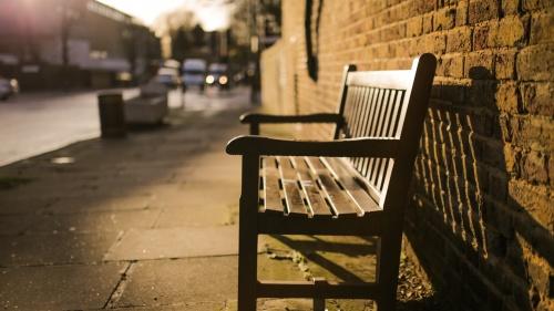 A empty bench on a sidewalk.