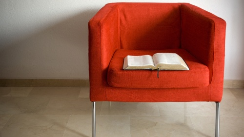 Bible laying in an empty red chair.