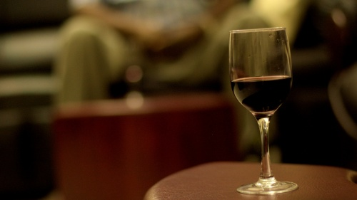 A glass of wine in the foreground and person sitting the background