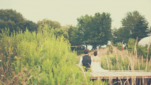 Married couple - man and woman - sitting on a dock.