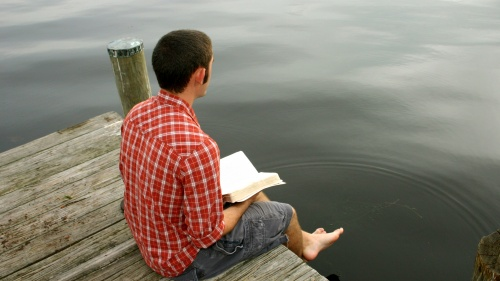 A man sitting on a dock reading a Bible.