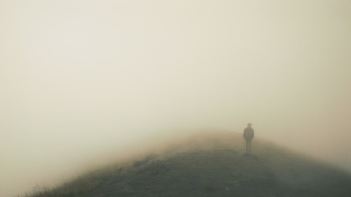 A man on top of hill that is surrounded in fog.