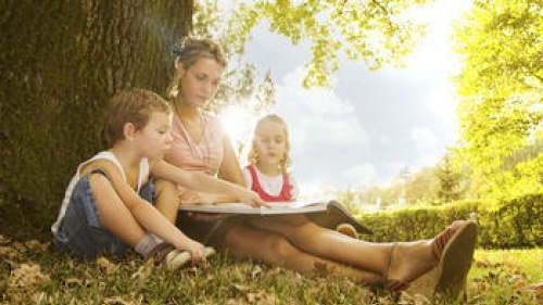 A mother reading to two children sitting outside.
