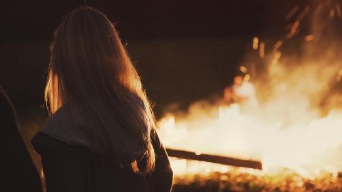 A woman standing by a bonfire.