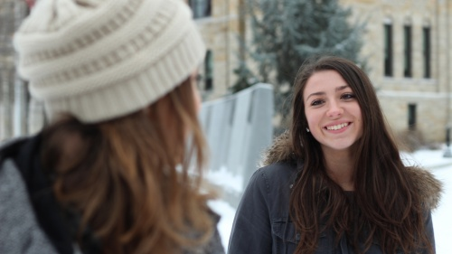 Two young adult women talking to each other while being outside in the cold.
