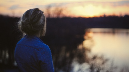 A young woman looking at the sun setting over water.