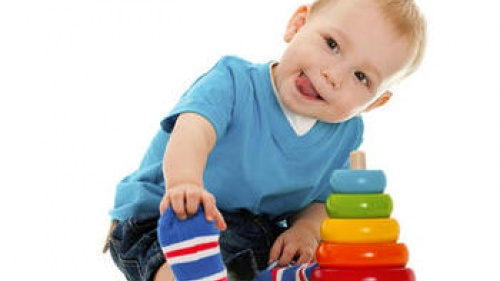 A baby playing with a stacking ring toy - Rock-a-stack