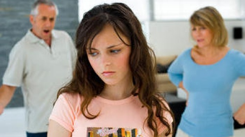 Teen girl in foreground with upset parents in background