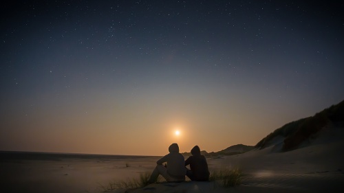 Two people sitting on a beach with the sun setting.