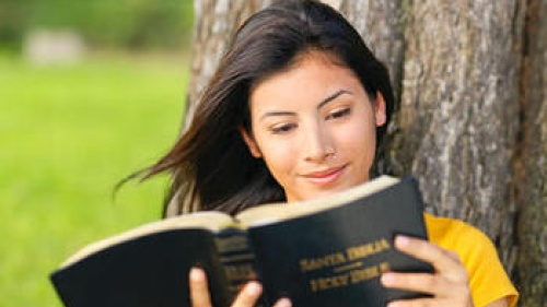 A young woman reading a Spanish version of the Bible (Santa Biblia).