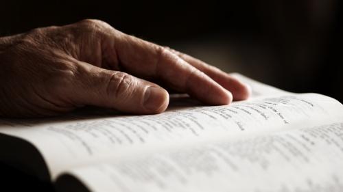An older man's hand on an open Bible.