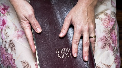 A Bible resting on the lap of a woman. Her hands on on top of the Bible.
