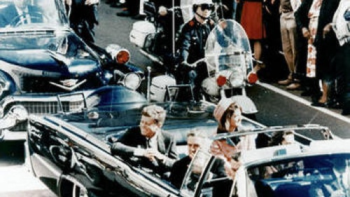President John F. Kennedy  riding in a motorcade in Dallas, Texas.