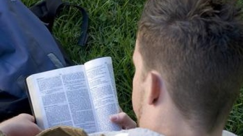 Young man reading a Bible.
