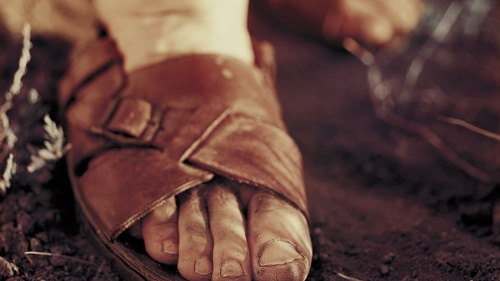 Dirty feet inside a pair of old sandals.