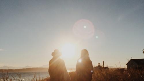 Two women walking toward a beach.