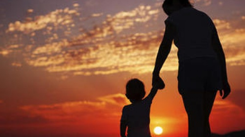 A mother holding her child's hand while watching the sun set.