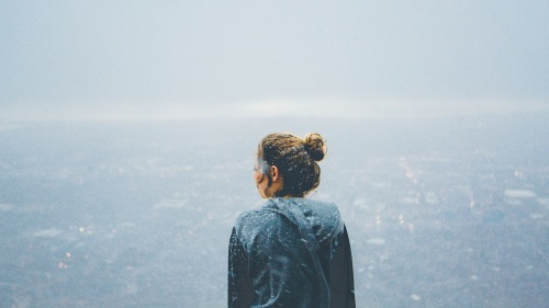 A young woman looking out over a cliff while it is snowing.