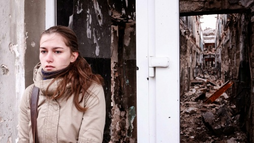 A young woman waits outside a building in Kurakhove, Eastern Ukraine.