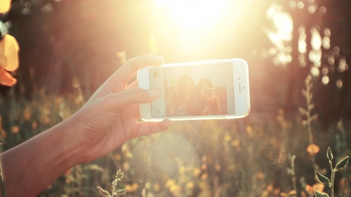"""Two young women taking a """"selfie"""" of themselves with the bright sun glaring."""