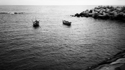 Small boats sitting in the bay of a sea.