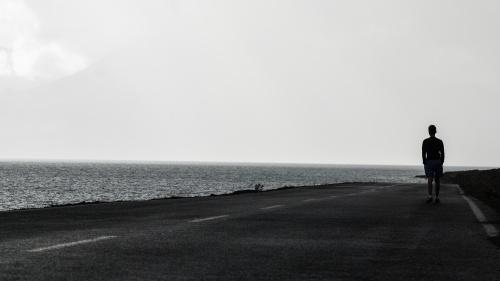 A man walking on a road beside a body of water.