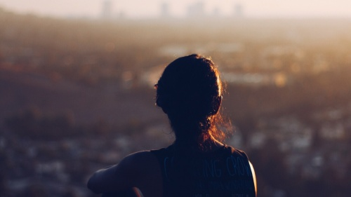 A woman sitting by herself on a cliff looking out over the town.