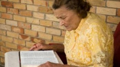 Older woman reading bible on a table - Understanding God's Word... What Is the G