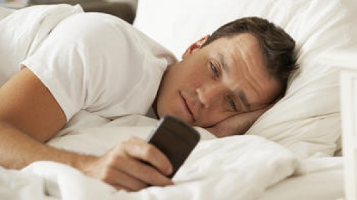 A man lying in bed staring at his smartphone.