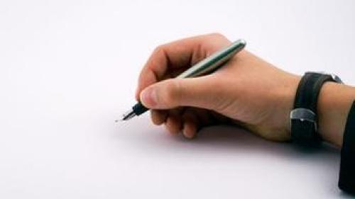 boy's hand holding pen