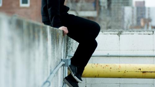 A person sitting on a concrete ledge.