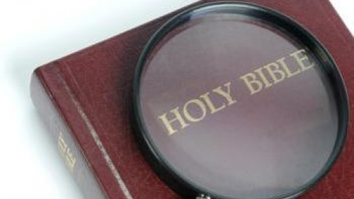 Magnifying glass over the words Holy Bible.