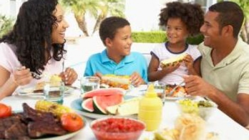 Parents and children around table with BBQ food - What Happened to the Family Me