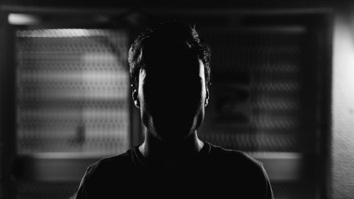 An upclose photo of a man but his face cannot be seen because of a shadow.