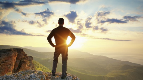 A young man on a cliff looking at the sunset.