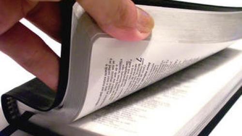hand opening Bible