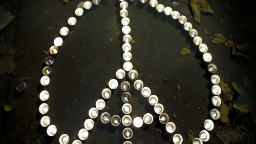 A piece sign incorporating the image of the Eiffel Tower using small candles.