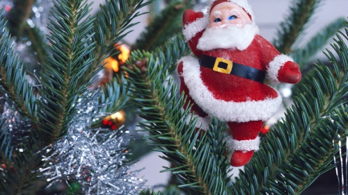 Santa Claus ornament hanging of tree.