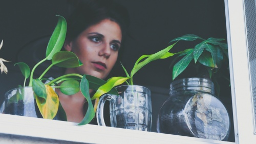 A woman looking outside a window with plants on the ledge.