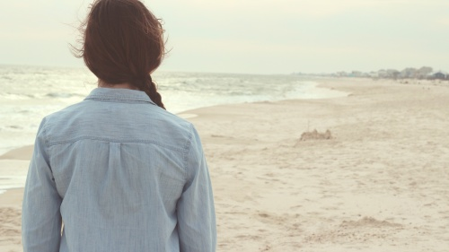 A young woman walking on the beach.