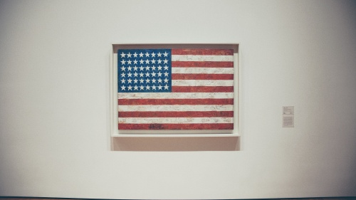 A framed old American flag hanging on a museum wall.