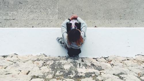 A woman sitting on a sidewalk.